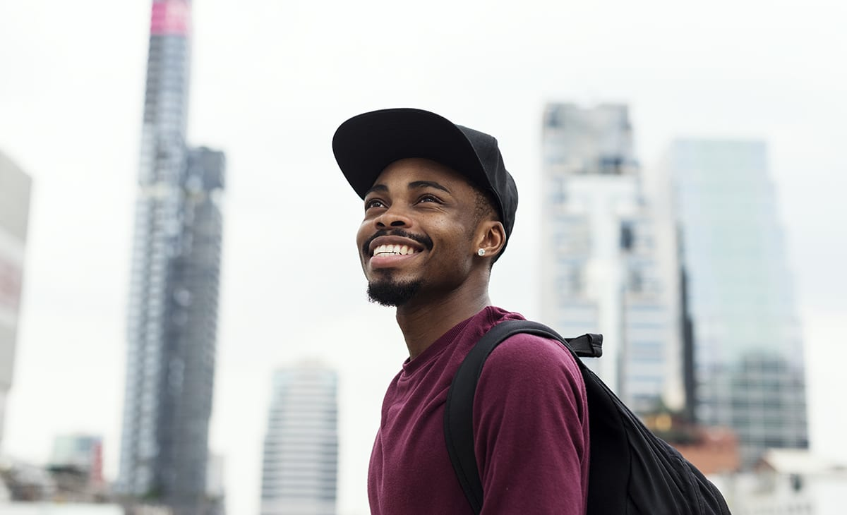 Man smiling in the city and looking at the sky
