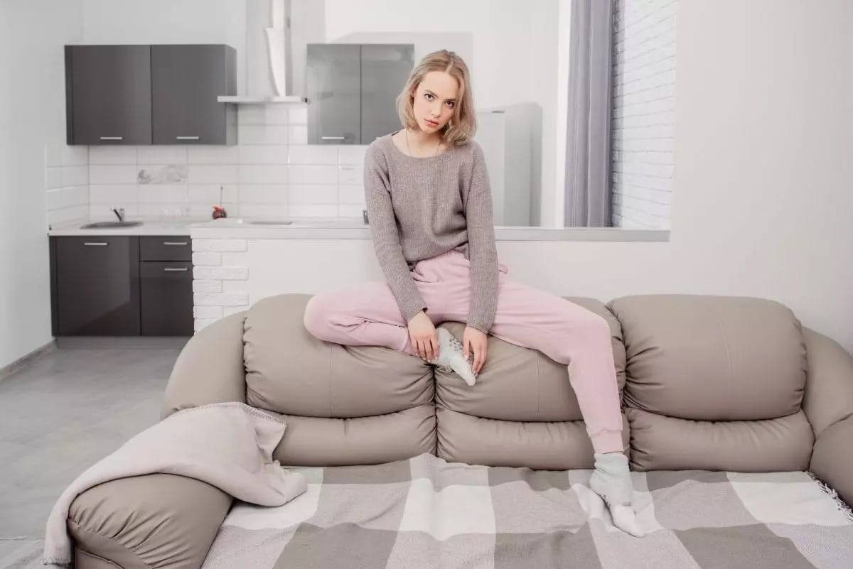 Young-Woman-Laying-On-her-Couch-in-Sweatpants