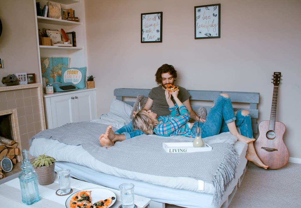Couple Lying on Bed Eating Pizza