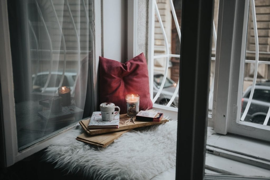 Coffee and Candles Next to a Window