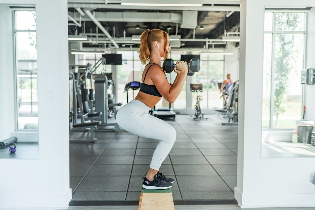 Woman doing squats at the gym