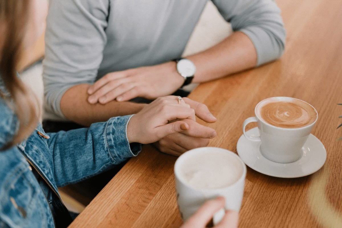 Couple Drinking Coffe and Holding Hands